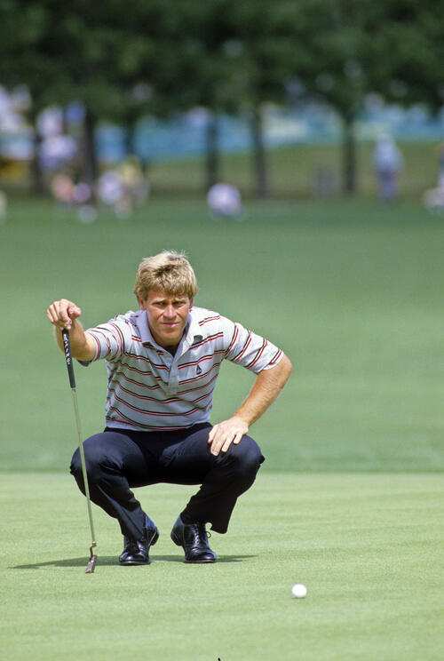 Hal Sutton squatting to line up a putt during the 1986 Hertz Bay Hill Classic