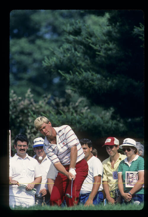 Hal Sutton hitting from the rough in front of the gallery during the 1984 US Open