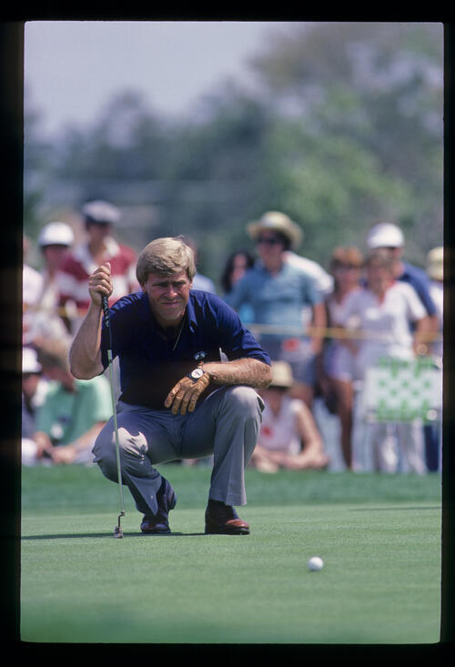 Hal Sutton squatting to line up a putt during the 1984 TPC