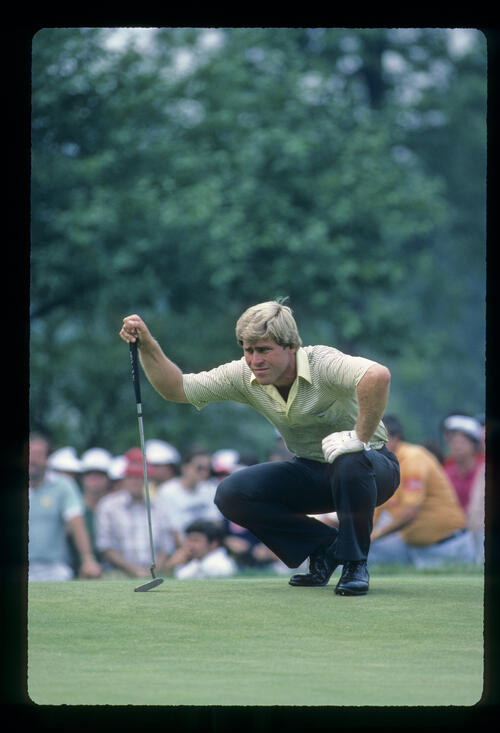 Hal Sutton squatting to line up a putt during the 1983 US Open