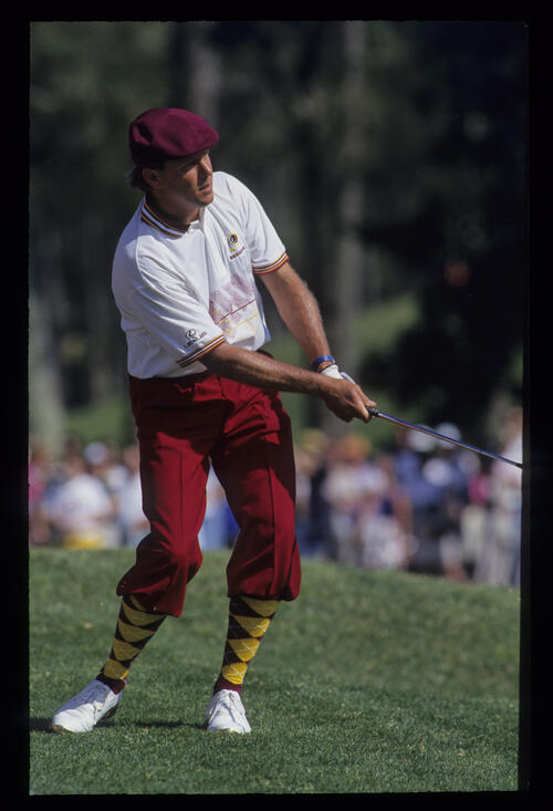 Payne Stewart, in red plus fours, pitching to the green during the 1993 TPC