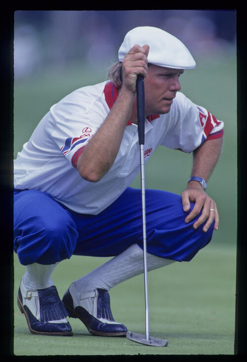 Payne Stewart crouching to line up a putt during the 1993 TPC