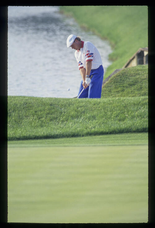 Payne Stewart pitching from the edge of a water hazard during the 1993 TPC