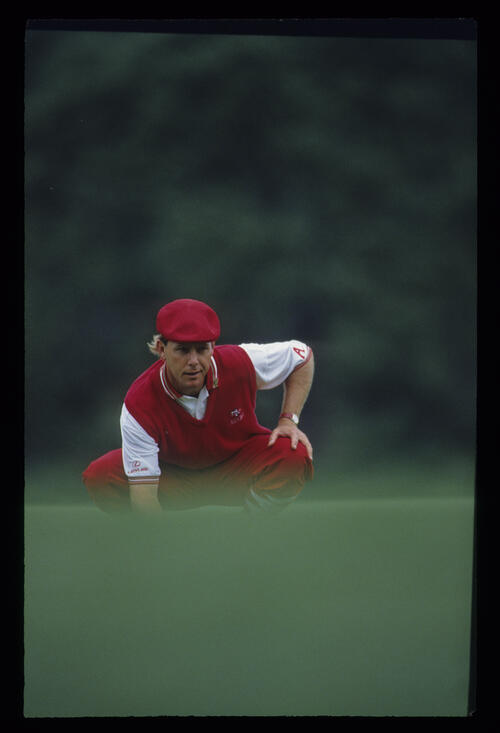 Payne Stewart squatting behind the line of a putt during the 1993 Masters