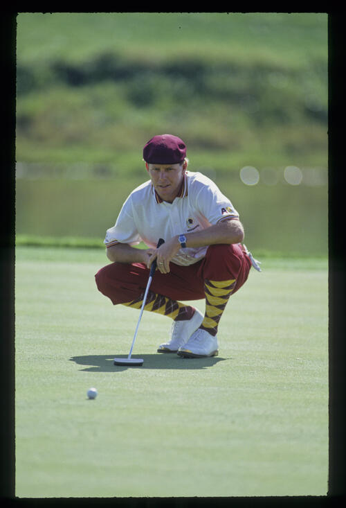 Payne Stewart crouching behind a putt during the 1993 TPC