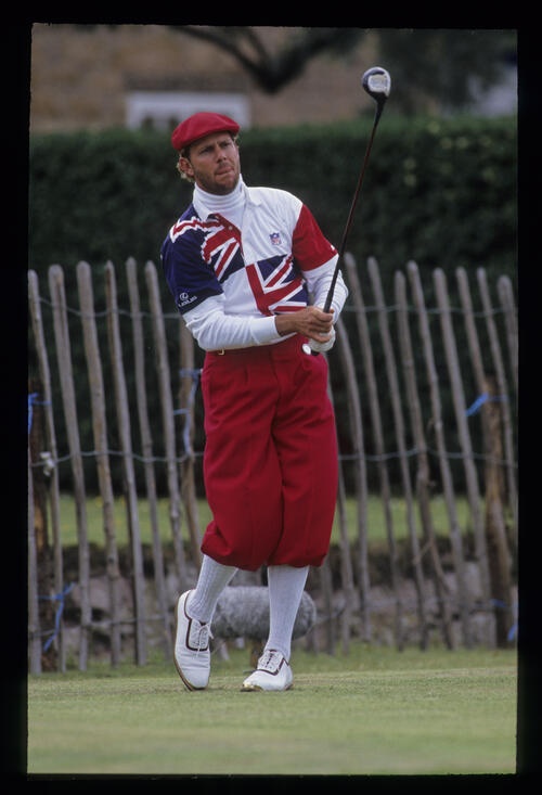 Payne Stewart, well wrapped up, following his ball flight after hitting driver on the tee during the 1992 Open Championship