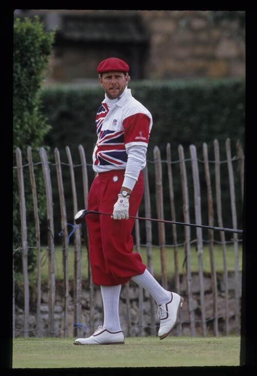 Payne Stewart, well wrapped up, still watching his ball while walking off the tee during the 1992 Open Championship