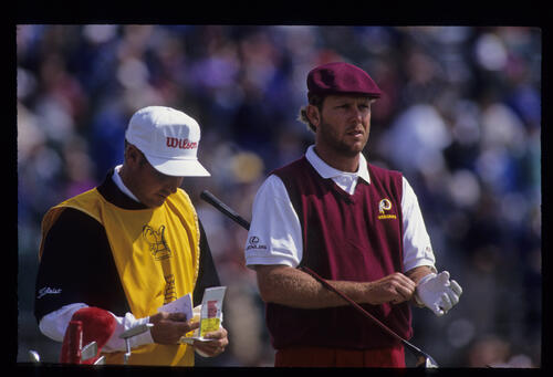 A bearded Payne Stewart and his caddie collaborating on the tee during the 1992 Open Championship