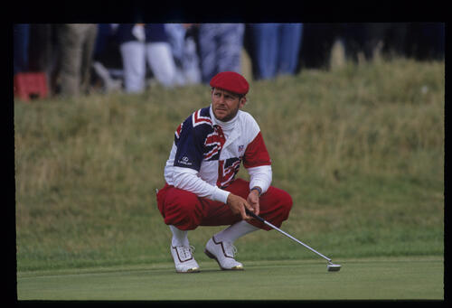 A bearded Payne Stewart squatting as he waits his turn to putt during the 1992 Open Championship