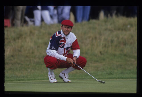 A bearded Payne Stewart crouching on the green as he waits his turn to putt during the 1992 Open Championship