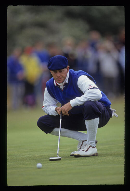 Payne Stewart crouching to line up a putt during the 1991 Open Championship