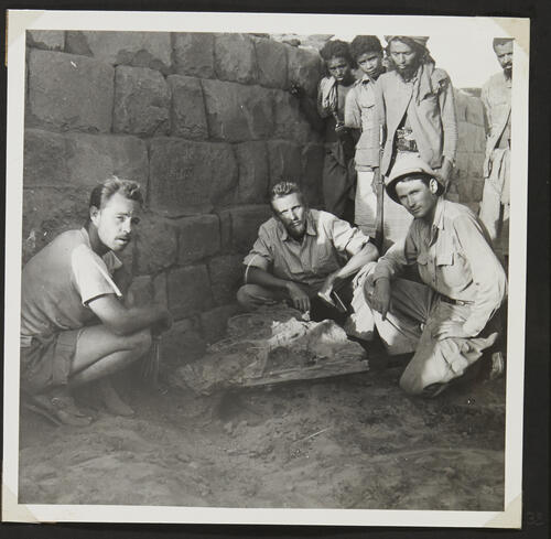 [Men sitting next to objects found during the excavations]