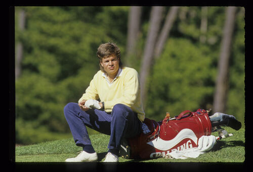 Johnny Miller Jr sitting on his golf bag during the 1988 AT&T