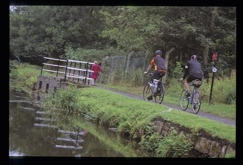 Cyclists passing the canal overspill, the Union Canal.