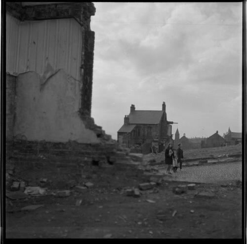 [Three unidentified people among ruined buildings, Rye Hill]