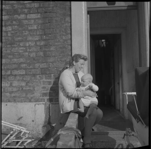 [An unidentified woman with baby sitting on a small brick wall in front of a doorway, Rye Hill]