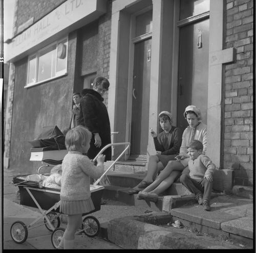 [Group of unidentified women, small children and prams in front of a set of doors, Rye Hill]