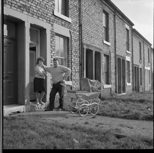 [Unidentified man, woman and pram standing in front of row houses, Rye Hill]