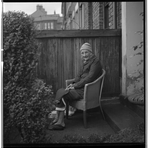 [Portrait of an unidentified elderly woman wearing a hat sitting in a chair in front of a wooden fence, Rye Hill]
