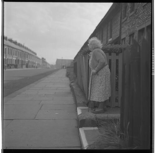 [An unidentified older woman with a cane standing on a step next to the pavement looking away from the camera, Rye Hill]