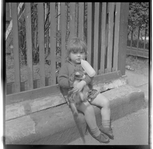 [Portrait of an unidentified small child holding a cat and drinking a bottle, Rye Hill]