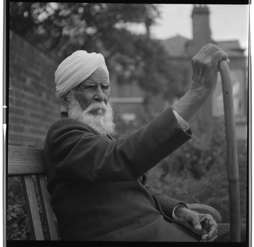 [An unidentified man with a white beard and a turban sitting on a bench holding a walking stick or cane, Rye Hill]