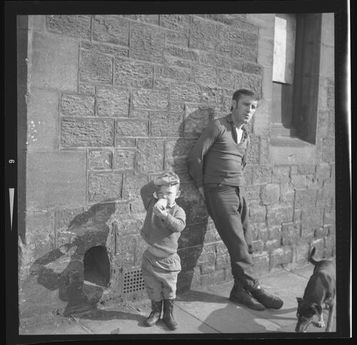[An unidentified man, a small child and a dog standing on the pavement, Rye Hill]