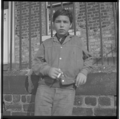[Portrait of an unidentified young boy smoking a cigarette leaning against a wall, Rye Hill]