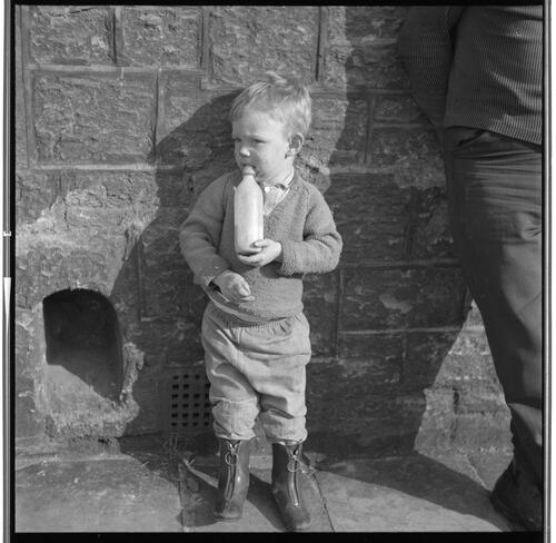 [Portrait of an unidentified small child standing against a wall drinking a bottle, Rye Hill]