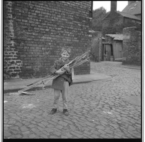[An unidentified small child carying a pile of sticks on a cobblestone street, Rye Hill]