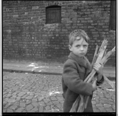 [An unidentified small child carrying a pile of sticks on a cobblestone street, Rye Hill]