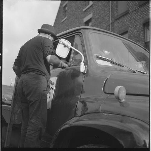 [An unidentified man talking to another man through a window of a lorry, Rye Hill]