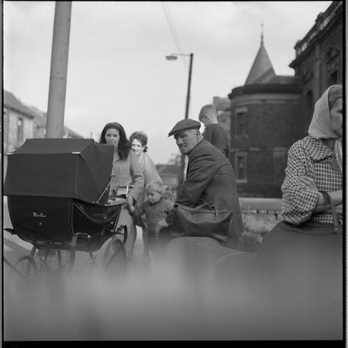 [An unidentified man sitting on a bench as a woman with a pram walk by, Rye Hill]