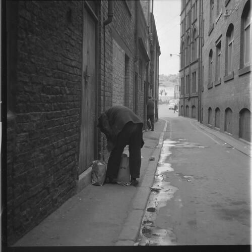 [An unidentified man bent over picking up bags in the street, Rye Hill]