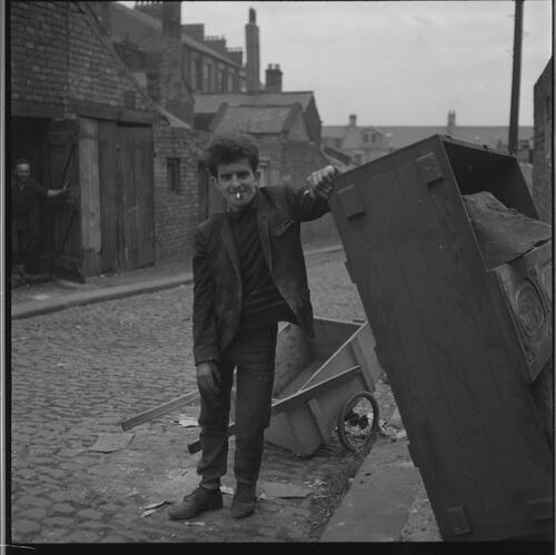 [Portrait of a small unidentified man smoking a cigarette standing in the street next to a wooden crate, Rye Hill]