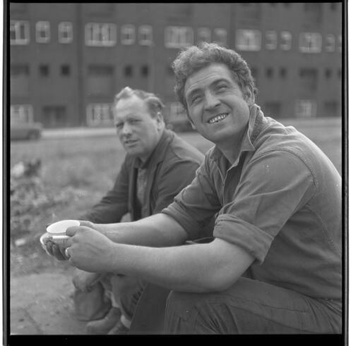 [Two unidentified men sitting outside, one of whom is holding a cup, Rye Hill]