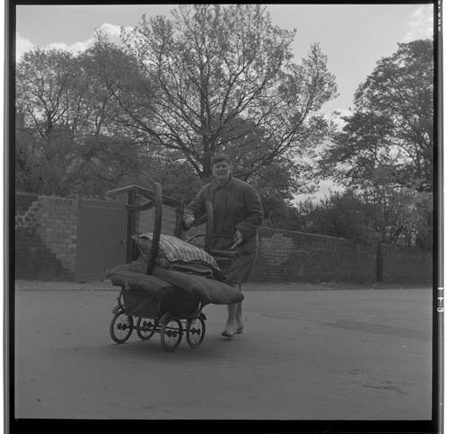 [Unidentified woman walking with a chair and pillows on a childs buggy, Rye Hill]