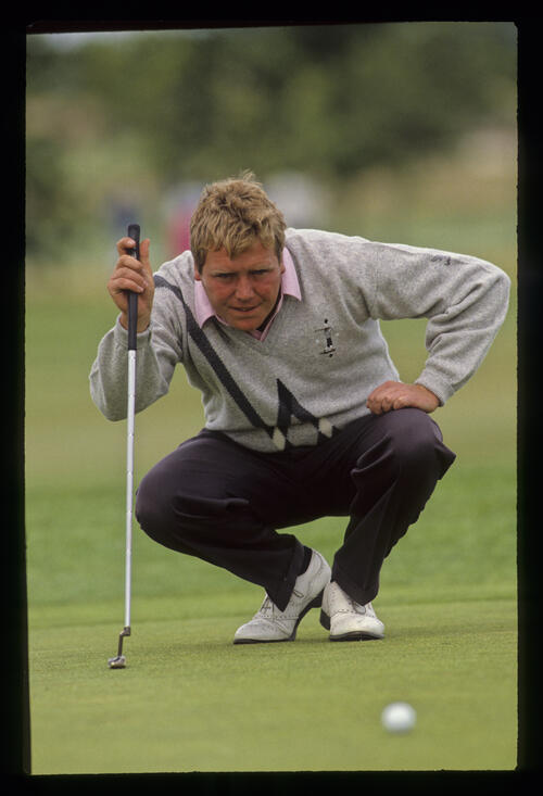 Richard Boxall squatting to line up a putt during the 1990 NM English Open