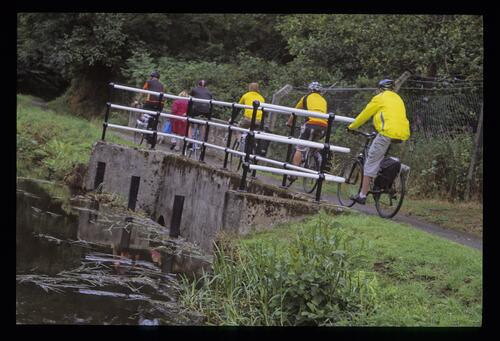 Cyclists crossing over a Union Canal overspill.
