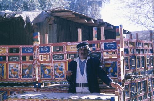 Unidentified man standing next to painted wooden Islamic textiles