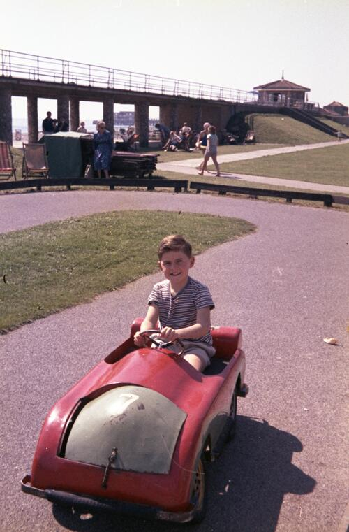 Unidentified boy in a small toy car