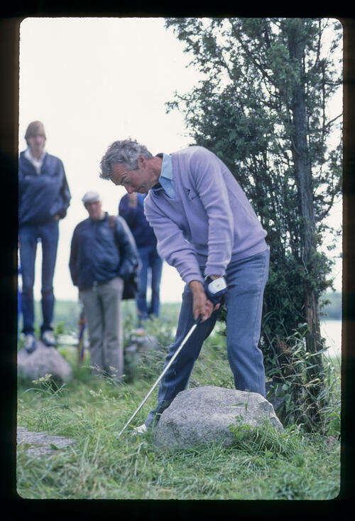 Brian Waites playing from behind a rock during the 1983 Scandinavian Enterprise Open