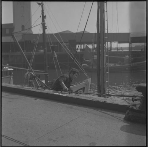 [A man in a boat holds on to a peg on the dock, South Shields fishing docks]