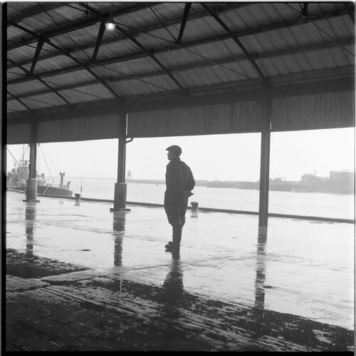 [Man standing on an empty section of a building, South Shields fishing docks]