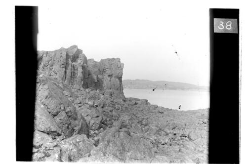 Cliffs on the Little Cumbrae with Millport in the distance.