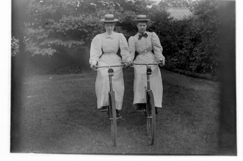 Two ladies (sisters) on bicycles [in the garden Cleveland Cottage, Isleworth].