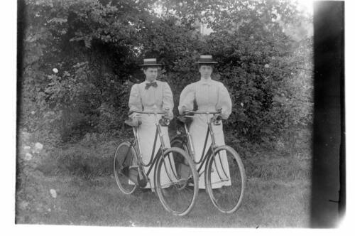 Two ladies (sisters) off bicycles [in the garden Cleveland Cottage, Isleworth].