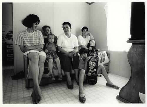 [Portrait of a group sitting at home, including women and children]