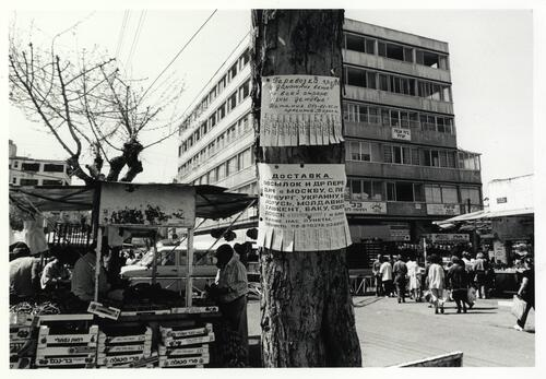 [Street advertisements in Hebrew and Russian, with a fruit stall on the back and a five-storey building]