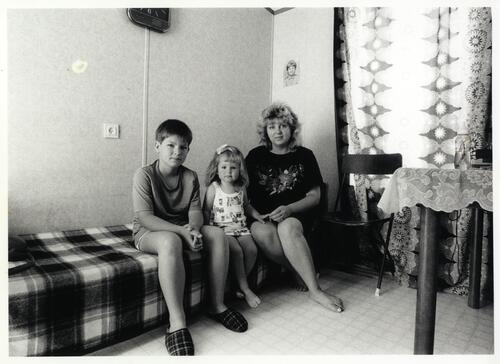 [A woman sitting with two children on a low couch or bed]